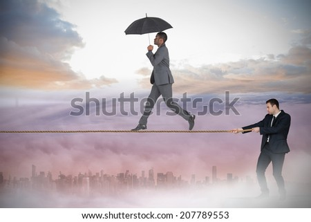 Young businessman pulling a tightrope for business man against cityscape in the clouds - stock photo