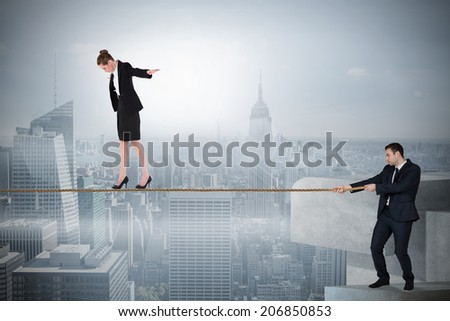Young businessman pulling a tightrope for business woman against misty cityscape - stock photo