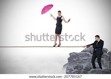 Young businessman pulling a tightrope for businesswoman against rocky landscape - stock photo