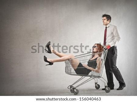 young businessman pushing shopping cart with inside a beautiful woman - stock photo