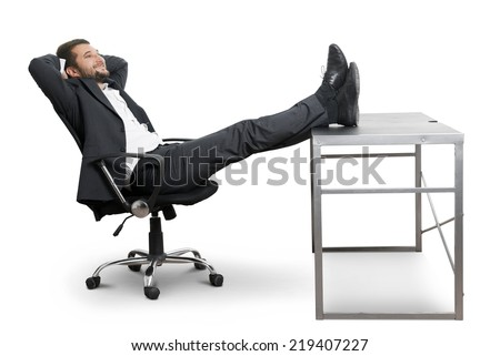 young businessman put his feet up on the table, resting and smiling. isolated on white background - stock photo