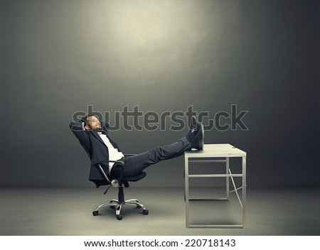 young businessman put his feet up on the table, resting and smiling. photo in the dark room - stock photo