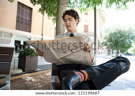 Young businessman reading a financial newspaper while sitting on a bench in the city, wearing quirky and colorful stripy socks. - stock photo