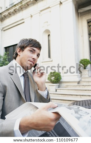 Young businessman reading a newspaper while sitting in a coffee shop's terrace. - stock photo