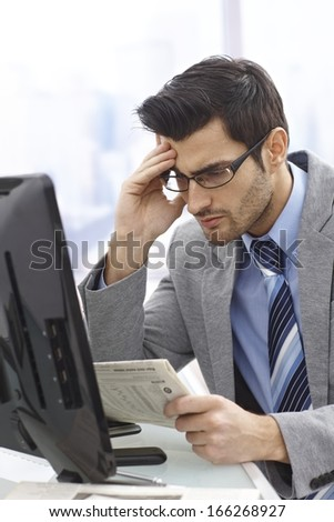 Young businessman reading bad news in financial newspaper. - stock photo