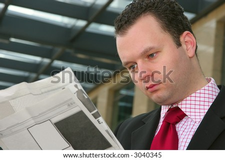 Young businessman reading blank newspapers - stock photo