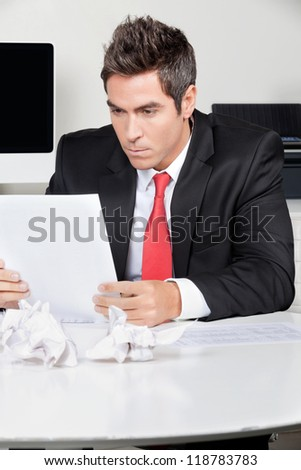 Young businessman reading document at desk in office - stock photo