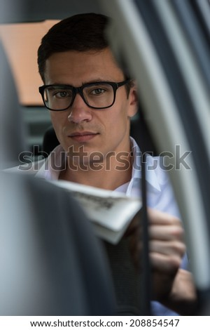 Young businessman reading newspaper on back seat of his car - stock photo