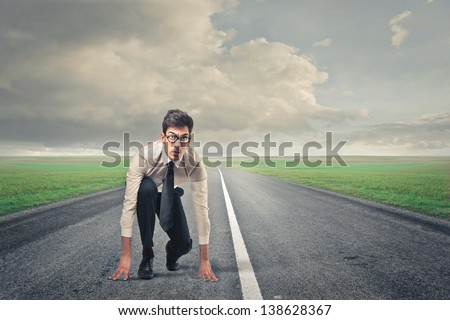 young businessman ready for the race on the road - stock photo