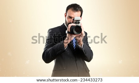 Young businessman recording video over ocher background.  - stock photo