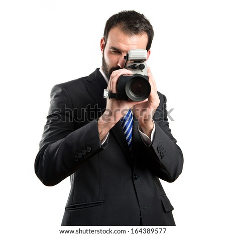 Young businessman recording video over white background - stock photo