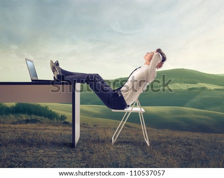 Young businessman relaxing at his desk in the middle of a green meadow - stock photo