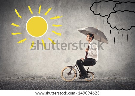 young businessman rides a bike with umbrella - stock photo