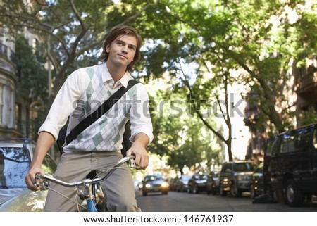 Young businessman riding bicycle on urban street - stock photo