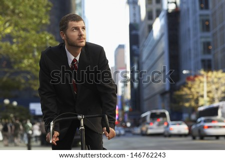 Young businessman riding bicycle while looking away on urban street - stock photo
