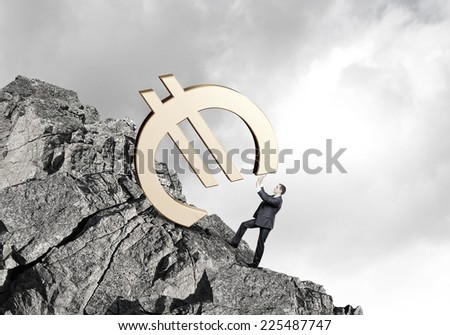 Young businessman rolling up the hill big euro sign - stock photo