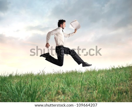 Young businessman running on a green meadow with documents in his hand - stock photo