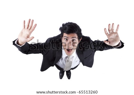 Young businessman screaming and scared with his arms up (above view isolated on white) - stock photo