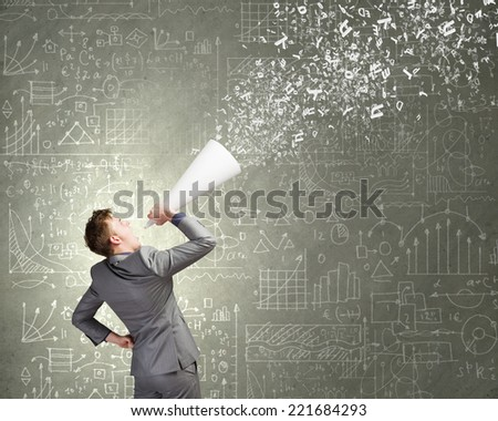Young businessman screaming emotionally in paper trumpet - stock photo