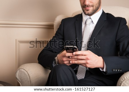 Young businessman sending message with mobile phone sit on armchair.  - stock photo