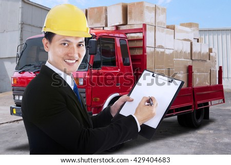 Young businessman showing clipboard while smiling at the camera with a distribution truck on the background - stock photo