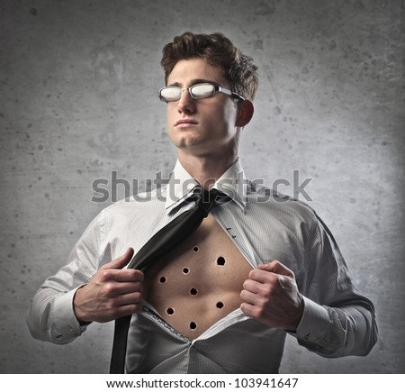 Young businessman showing his chest full of bullet holes - stock photo