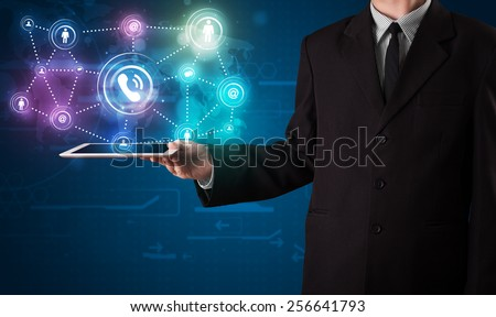 Young businessman showing social networking technology with colorful lights - stock photo
