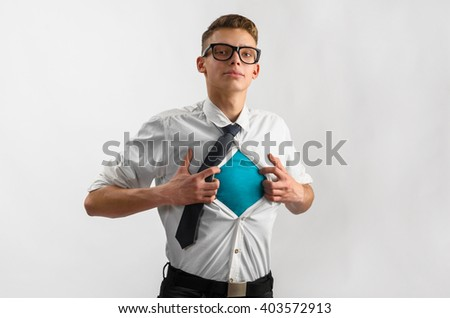 Young businessman showing suit of super hero with copy space under his shirt and tie on gray background - stock photo