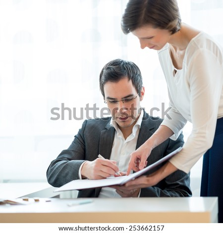 Young Businessman Signing a Document Hold by his Female Secretary While Sitting at his Worktable Inside the Office. - stock photo