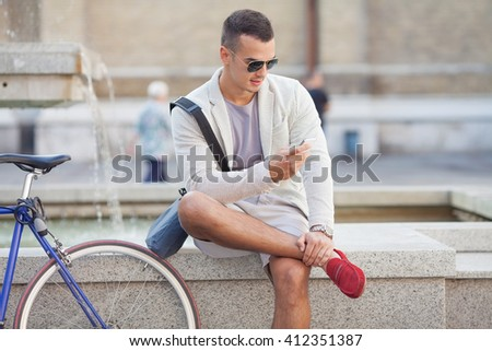 Young businessman sitting at a fountain and using his phone. There is his bicycle beside him. - stock photo