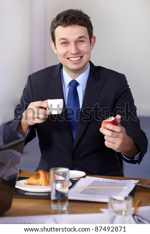 Young businessman sitting at conference table have a break during meeting, holds coffee cup and apple - stock photo