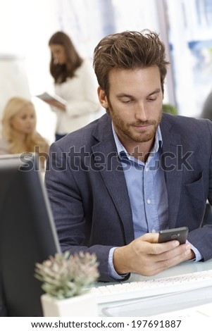 Young businessman sitting at desk in office, using mobilephone. - stock photo