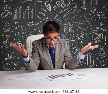 Young businessman sitting at desk with business scheme and icons - stock photo