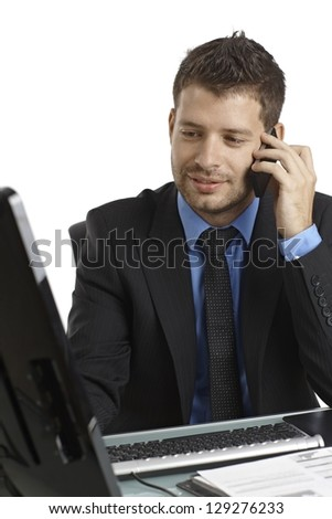 Young businessman sitting at desk, working with computer, talking on mobilephone. - stock photo