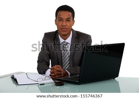 Young businessman sitting at his desk - stock photo