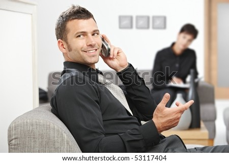 Young businessman sitting at office lobby talking on mobile phone, smiling. - stock photo