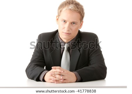 Young businessman sitting behind the desk isolated - stock photo