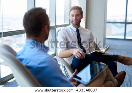Young businessman sitting comfortably in an open modern office, smiling while having a positive conversation with a coworker - stock photo