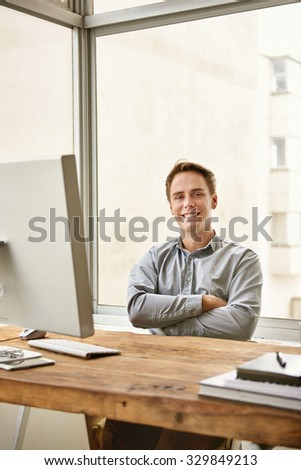 Young businessman sitting confidently with his arms folded behind his desk in a bright office  - stock photo
