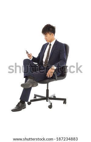 Young businessman sitting in a chair and watching smartphone - stock photo