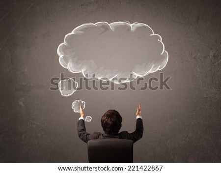 Young businessman sitting in office chair in front of a wall with cloud thought sketched on a chalkboard above his head - stock photo