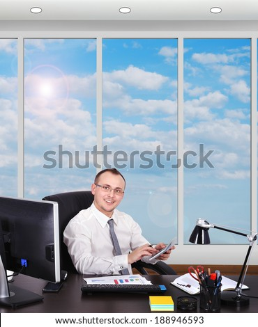 young businessman sitting in office with  phone - stock photo