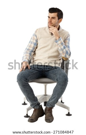Young businessman sitting in swivel chair over white background, thinking, looking away. Hand on chin. - stock photo