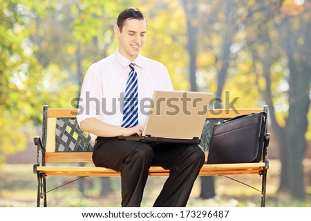 Young businessman sitting on a bench and working on a laptop in a park - stock photo