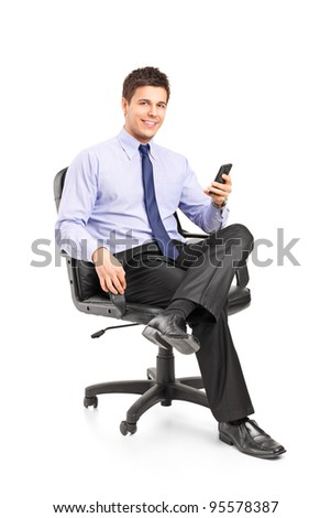 Young businessman sitting on a chair and holding a mobile phone isolated on white background - stock photo