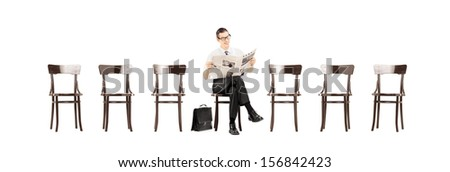 Young businessman sitting on a wooden bench and reading a newspaper while waiting isolated on white background - stock photo