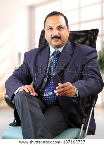 Young businessman sitting on chair at his office and keeping specs on his hand. - stock photo