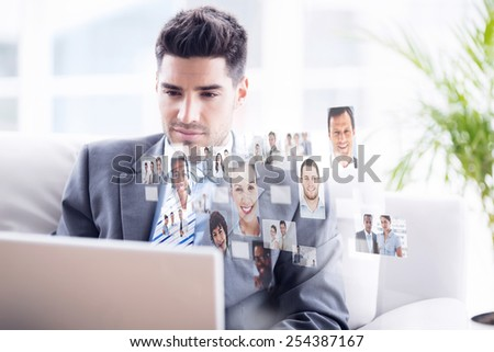 Young businessman sitting on couch using his laptop against business people - stock photo