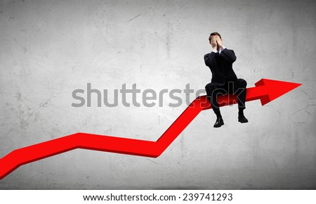 Young businessman sitting on red arrow with closed eyes - stock photo