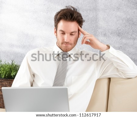 Young businessman sitting on sofa, working on laptop. - stock photo